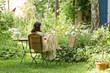 canvas print picture - Junge Frau im Garten ließt ein Buch