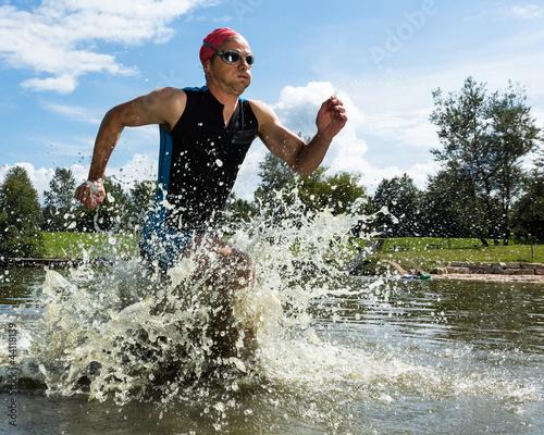 Photo  Triathlet rennt aus dem Wasser