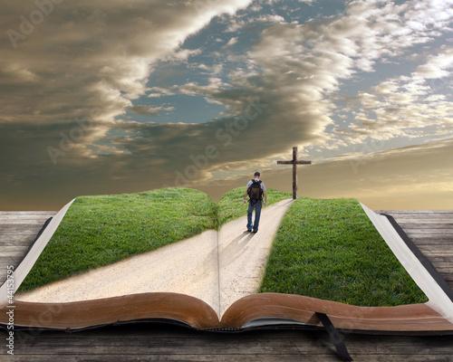 otwarta-biblia-z-droga-po-ktorej-idzie-czlowiek-w-kierunku-krzyza
