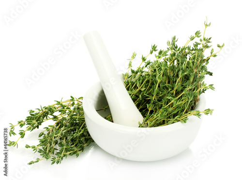Fotografía  mortar with fresh green thyme isolated on white