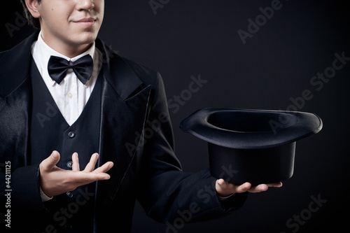 Fotografie, Obraz  closeup of magician showing tricks with top hat isolated