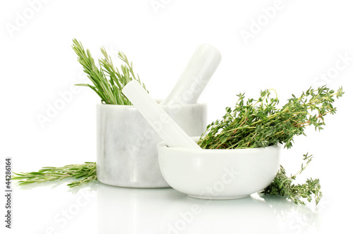 Fotografía  mortars with fresh green thyme and rosemary isolated on white