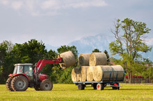Tractor Lifting Hay Bale On Ba...