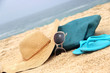Blue beach bag on the seacoast and straw hat