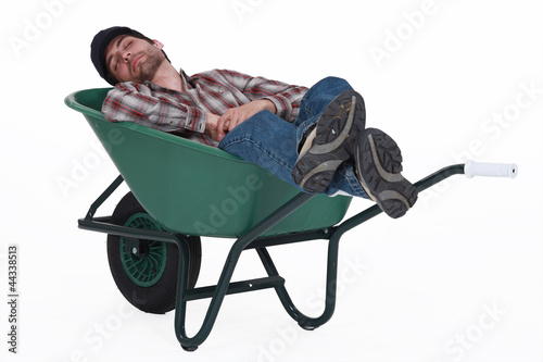 Fotografía  Worker taking a nap in wheelbarrow