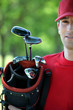 Golfer holding golf bag.