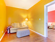 Orange and pink rooms with sofas and hardwood floor.