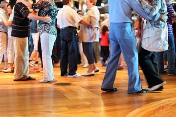 Fototapeta Many happy senior couples in love dancing on wooden dance floor.
