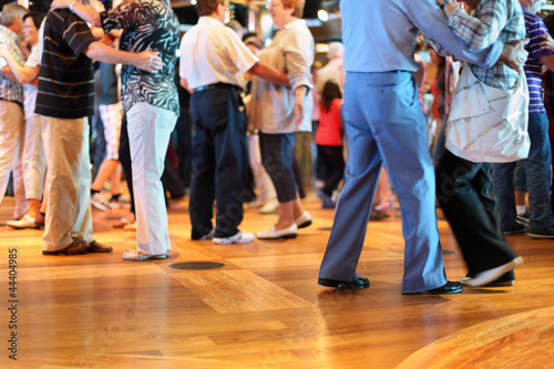 Tuinposter Dance School Many happy senior couples in love dancing on wooden dance floor.