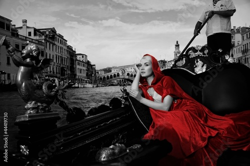Poster de jardin Photo du jour Beautifiul woman in red cloak riding on gandola