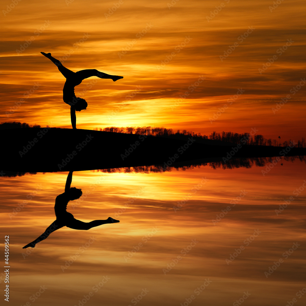 Fototapety, obrazy: silhouette of female gymnast doing a handstand in sunset