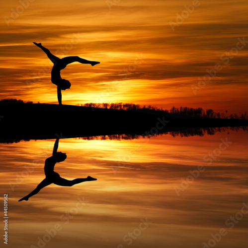 Fototapeta silhouette of female gymnast doing a handstand in sunset obraz