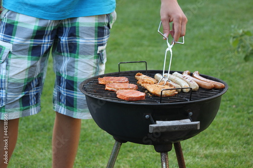 garten grill, mann grillt bratwurst im garten nahaufn. grill - buy this stock, Design ideen