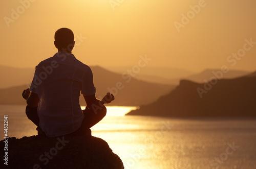 Fototapety, obrazy: Guy meditating at sunset