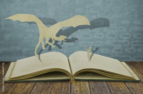 Vászonkép Paper cut of dragon and child hold sword on old book