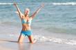 young happy woman in blue bikini on sea background