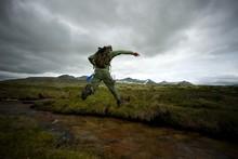 Man Hiker Jumping Across Small River