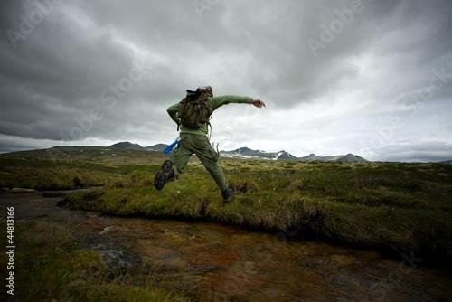 Fototapeta Man hiker jumping across small river obraz