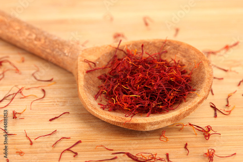 stigmas of saffron in wooden spoon on wooden background