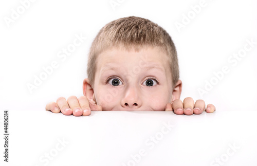 Fototapeta chłopiec wyglądający zza stołu obraz