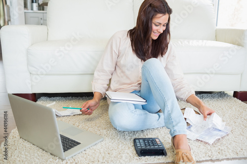 Fotografia, Obraz  Woman using laptop to calculate bills