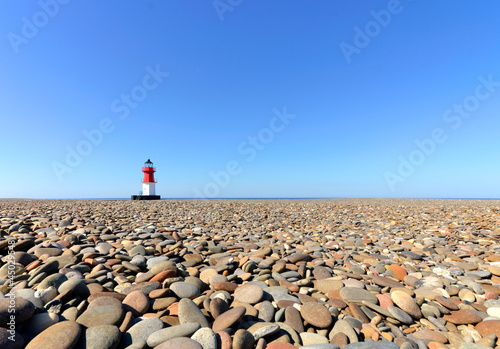 Photo  Lighthouse with Beach Pebbles in foreground