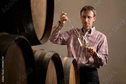 Fotografía  Winemaker in cellar making wine test.