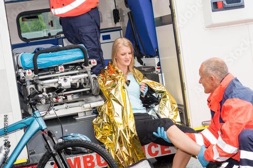Obraz Paramedics with woman bike accident in ambulance - fototapety do salonu