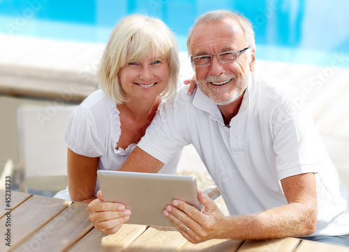 Fotografia, Obraz  Different aged couple using a tablet pc outside