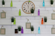 White Wooden Wall Decorated With Clock And Glass Bottles