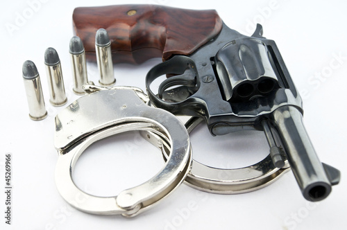 Fotografie, Obraz  handgun revolver and police handcuff with bullets on white backg