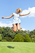 Beautiful young woman jump up to the sky in park in blue dress