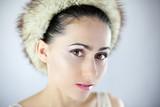Fototapeta Zwierzęta - Śliczna młoda dziewczyna w futrzanej czapce