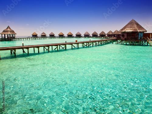 Staande foto Groene koraal Island in ocean, overwater villas
