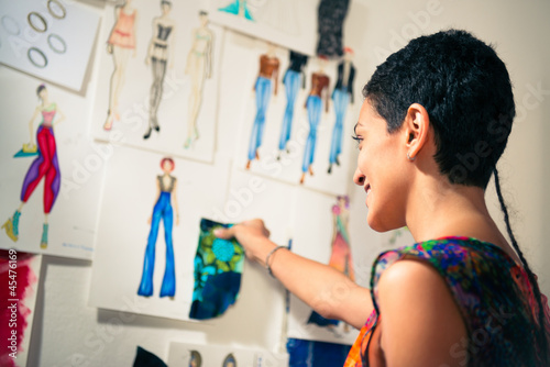 Fotografia, Obraz  Female fashion designer contemplating drawings in studio