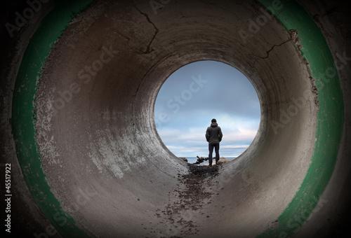 Fotografie, Obraz  Man looks at horizon in the end of dark concrete tunnel