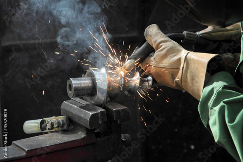 Welder doing arc welding of a steel shaft with helicoid - Buy this