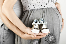 Newborn Baby Booties In Parents Hands. Close Up.