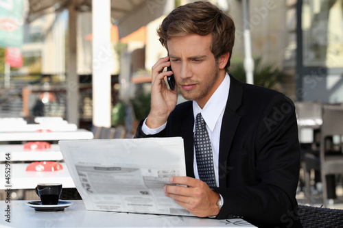 Fototapety, obrazy: Young man on phone while reading newspaper