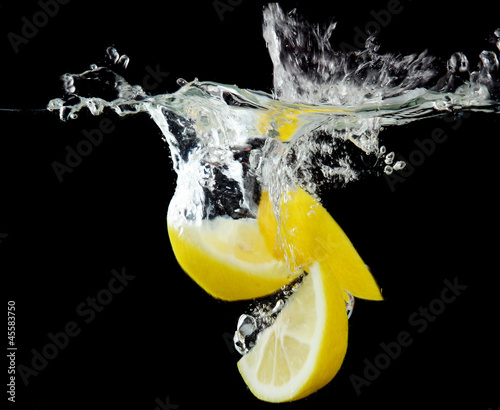 Poster Eclaboussures d eau Sliced lemon in the water on black background