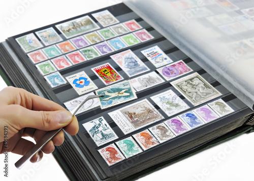 Fotografiet Hand holding postage stamp with tweezers over album