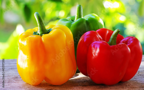 Photo  red, yellow and green pepper on table,green background