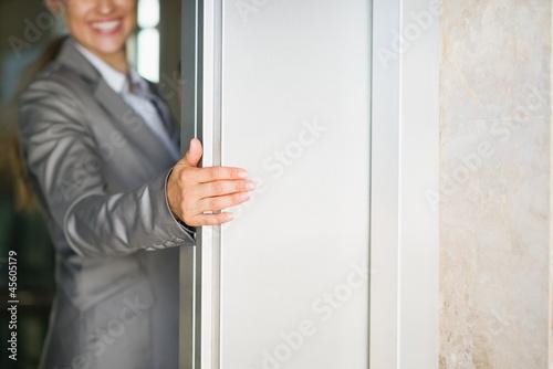 Photo  Closeup on business woman hand holding elevator door
