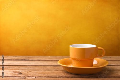Fototapeta Yellow coffee cup on wooden tabletop obraz na płótnie