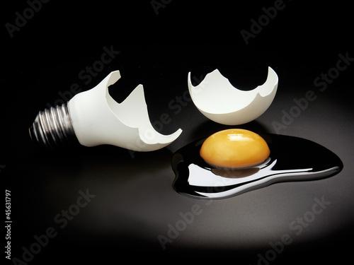 Concepto de un huevo abierto,cascara de huevo y bombillo roto.