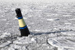 Conical black and yellow buoy on frozen Baltic sea
