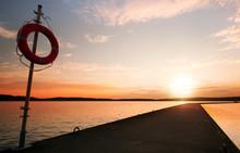 Safety Equipment. Lifebuoy On The Pier In The Orange Sunrise