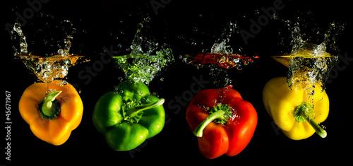 vier verschieden farbige Paprika fallen ins Wasser - 45671967
