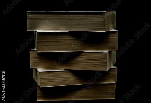 Obraz Sterta starych książek na czarnym tle - fototapety do salonu