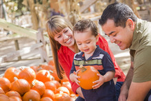 Happy Mixed Race Family At The Pumpkin Patch